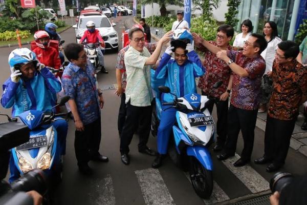 Presdir Astra International, Prijono Sugiarto memakaikan helm kepada salah satu peserta mudik. (foto : ai)