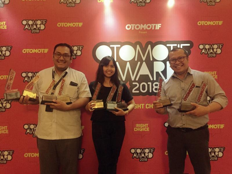 Manajer PR Toyota Astra Motor, Rouli Sijabat (kanan) kerepotan membopong trofi Otomotif Award. (foto : ist)