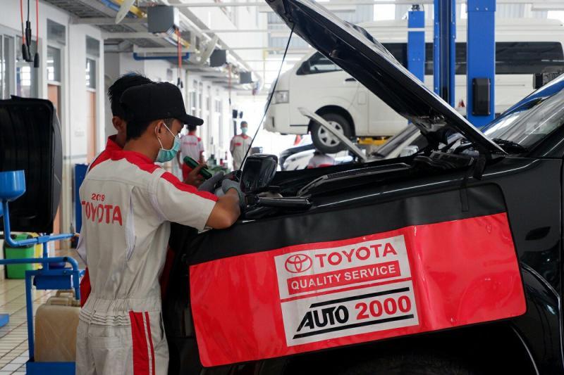Mekanik Auto2000 tengah menservice mobil Toyota milik pelanggan di bengkel Auto2000. (foto : ist)