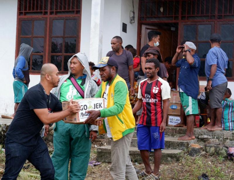 Mulawarman dari Gojek Peduli menyalurkan langsung bantuan korban banjir Jayapura, Papua. (foto : ist)
