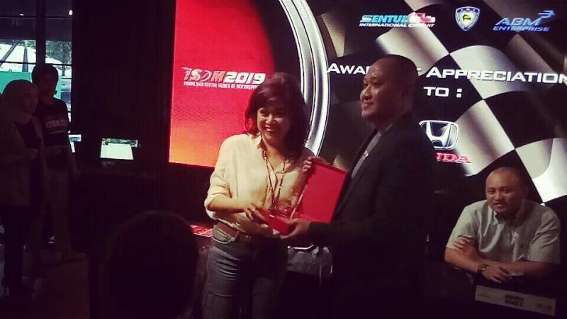 Alvin Bahar mewakili Honda menerima plakat dari Vivi Montolalu. (foto : bs)
