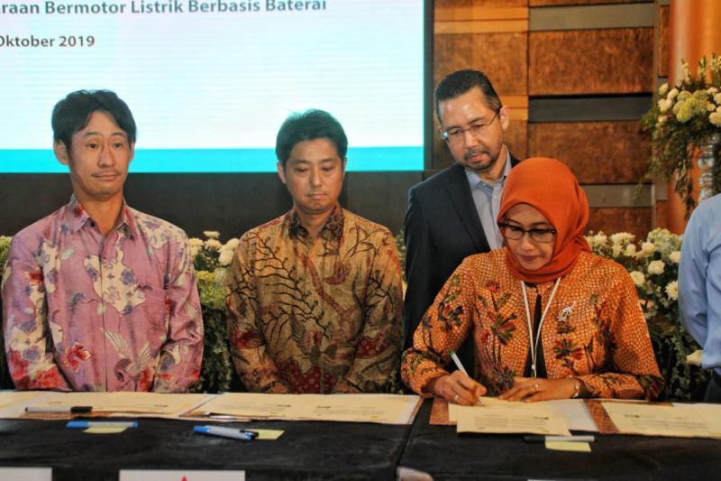 Naoya Nakamura, President Director PT MMKSI (tengah, berbatik) menyaksikan penandatanganan nota kesepahaman oleh PLT Direktur Utama PT PLN, Sripeni Inten Cahyani.  (foto: MMKSI)