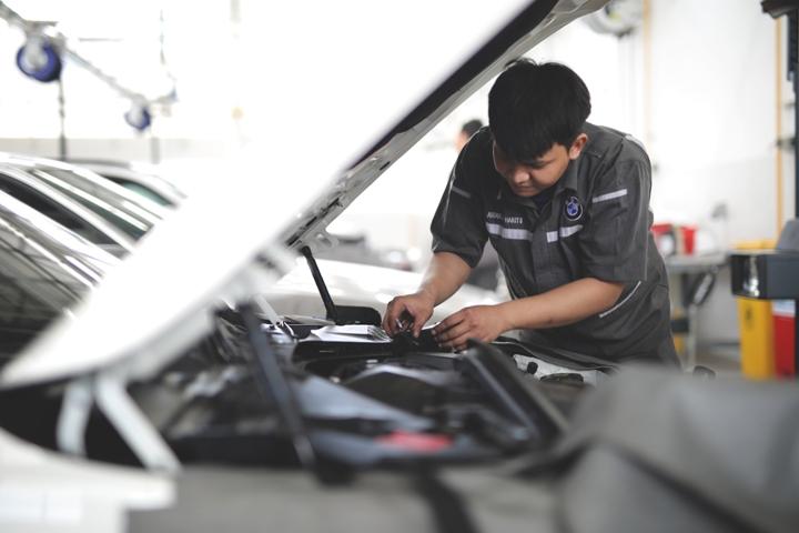Teknisi melakukan pemeriksaan mobil di bengkel BMW Astra. Foto personel: Personel bengkel BMW Astra siap melayani seluruh pemilik BMW dan MINI
