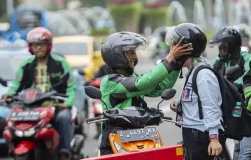Pengendara ojek online tengah memasangkan helm kepada penumpang, dibolehkan bawa penumpang dengan syarat. (katadata)