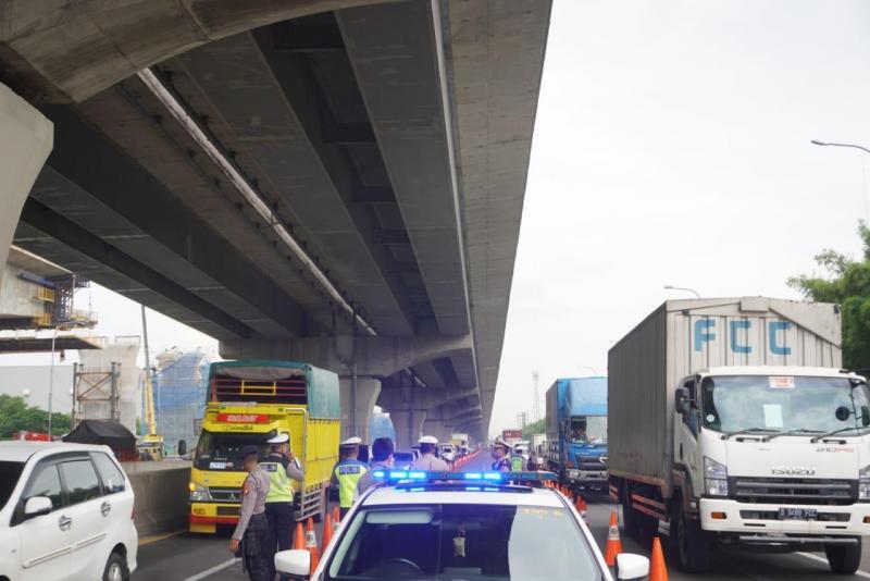 Petugas kepolisian melakukan penertiban kendaraan di jalan tol