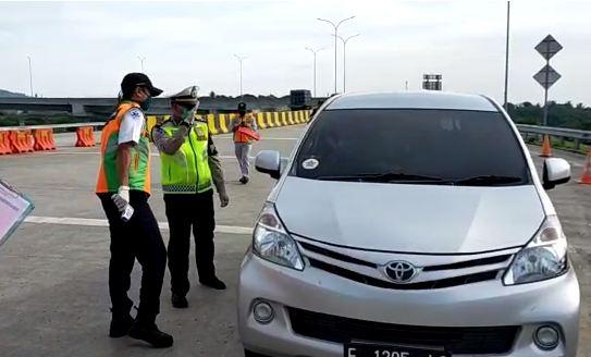 Polisi bersiaga di gerbang tol untuk memantau warga yang bandel tetap Mudik meski telah dilarang pemerintah.
