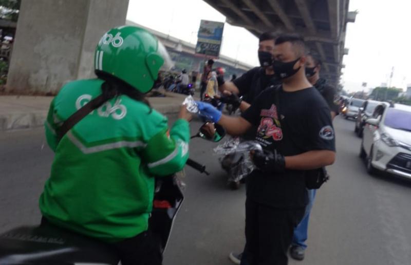 Rekan-rekan dari komunitas Bandit Community Indonesia membagikan masker kepada pengendara motor di Jakarta
