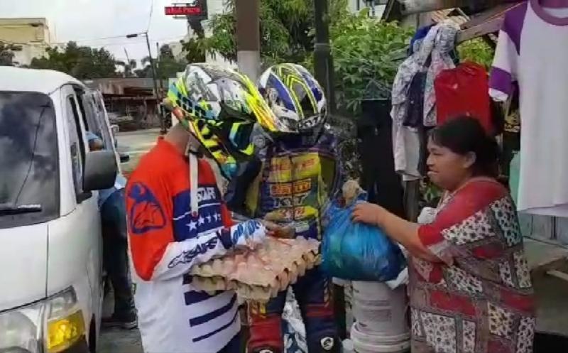 Pembalap lengkap dengan baju balap membagikan sembako pada IMI Sumbar Berbagi, Kamis (21/5/2020) hari ini.
