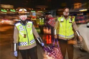 Petugas kepolisian membantu membawakan barang bawaan pemudik yang diputar balikkan di pintu tol Cikarang Barat. (foto : ist)