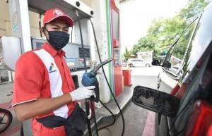Petugas SPBU selain harus membuka dan isi tangki bensin mobil konsumen, juga tetap jaga jarak minimal 1 meter. (foto : ist)