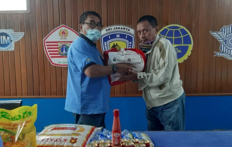 Donny SQ selaku Kabid Olahraga Mobil IMI DKI memberikan paket bansos kepada Jamain fotografer balap 3 zaman