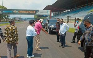 Menteri Suharso Monoarfa (tengah, baju putih) mendapat penjelasan H.Tinton Soeprapto terkait pengaspalan ulang sirkuit Sentul
