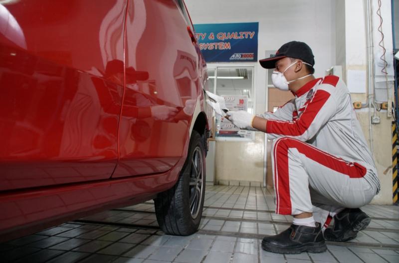 Seorang mekanik Auto2000 sedang melakukan perawatan bodi mobil pelanggan