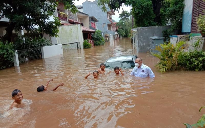 Anondo Eko berusaha membantu evakuasi mobil yang terseret arus banjir di kawasan Ciledug, Jakarta Selatan.