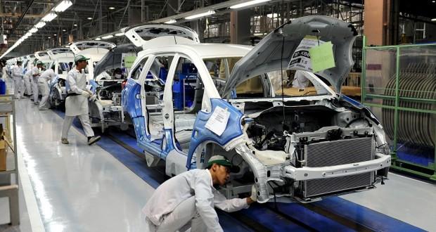 Seorang teknisi sementara memeriksa dan merakit mobil di sebuah pabrik otomotif