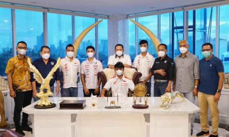 Aksi salah satu pembalap Astra Honda Racing Team asal Jawa Timur duduk di meja kerja Ketua MPR Bamsoet, sementara Bamsoet berdiri di belakangnya sambil tersenyum