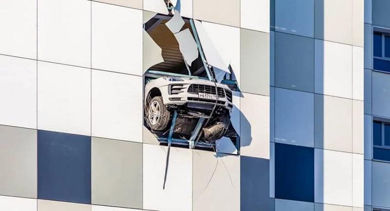 Sebuah Porche Macan nyaris terjun bebas setelah menabrak dinding parkiran di sebuah pusat perbelanjaan di Moskow, Rusia