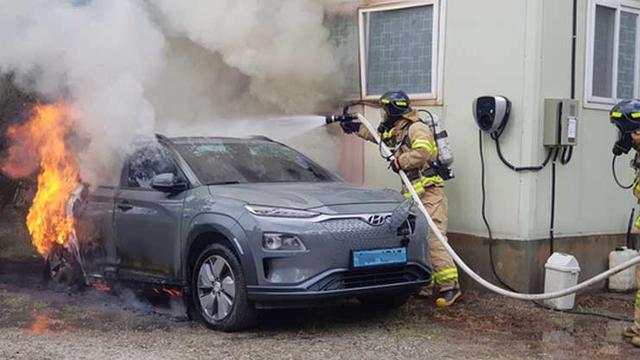 Petugas pemadam kebakaran menyemprot air pada unit Hyundai Kona yang terbakar karena masalah baterai