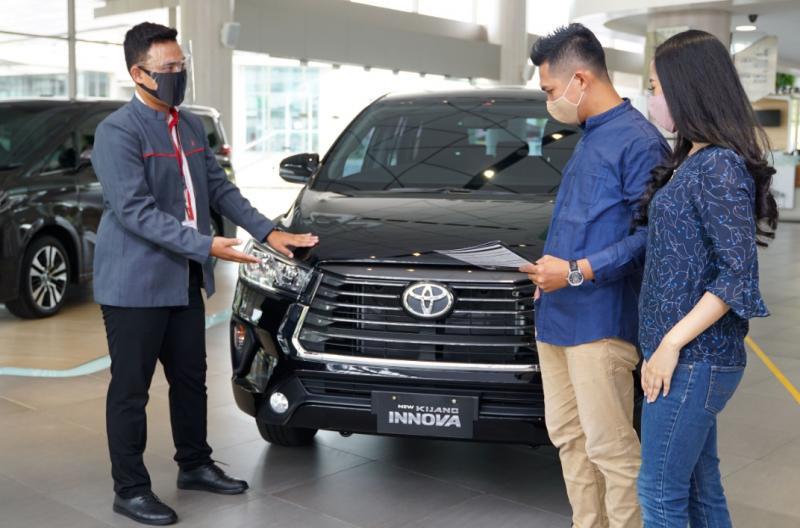 Petugas Auto2000 sedang menjelaskan keunggulan Kijang Innova ke AutoFamily