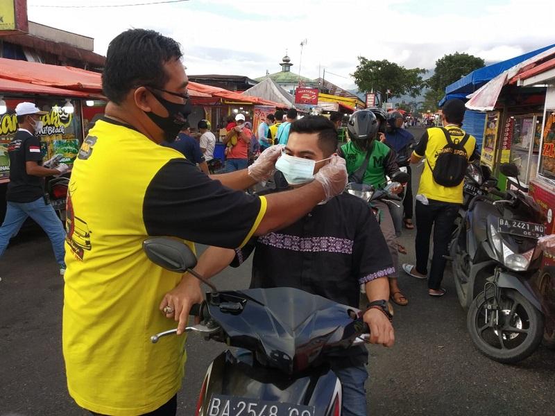 Salah satu member Innova Community (IC) memakaikan masker kepada pengendara motor di Padang Panjang