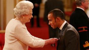 Lewis Hamilton (Inggris/Mercedes) saat menerima sebuah penghargaan dari Ratu Elisabeth. (Foto: sportrush)