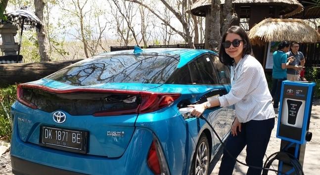 Seorang pengguna mobil listrik Toyota sementara melakukan pengecasan baterai