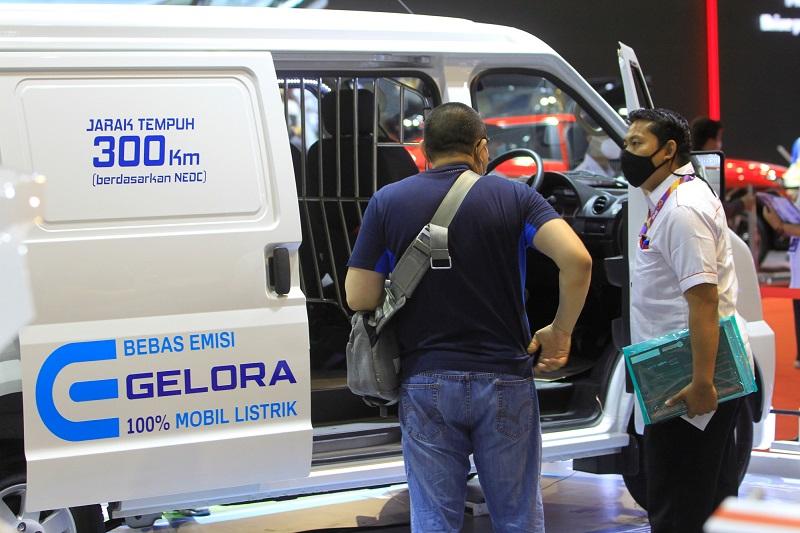 Seorang tenaga sales DFSK sementara melayani konsumen yang tertarik dengan DFSK Gelora E