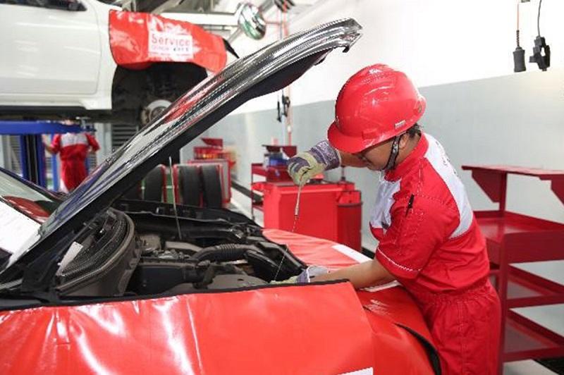 Ilustrasi teknisi Mitsubishi sedang melakukan pengecekan unit mobil konsumen saat servis