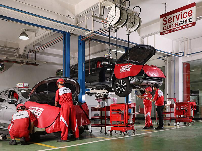 Ilustrasi teknisi Mitsubishi sementara melakukan pengecekan dan perawatan mobil konsumen di bengkel resmi