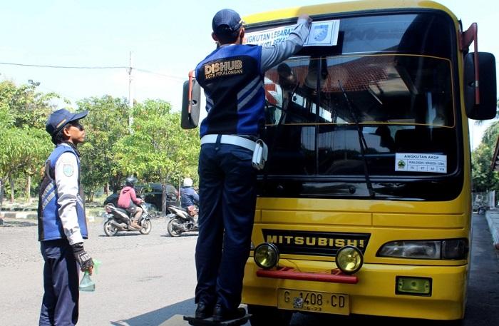 Petugas Dinas Perhubungan menempelkan stiker khusu untuk kendaraan umum Lebaran yang oleh mengangkut penumpang