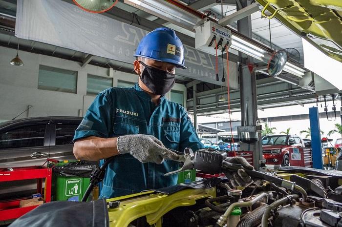 Teknisi Suzuki sementara melakukan pemeriksaan dan perawatan mobil konsumen di sebuah bengkel resmi