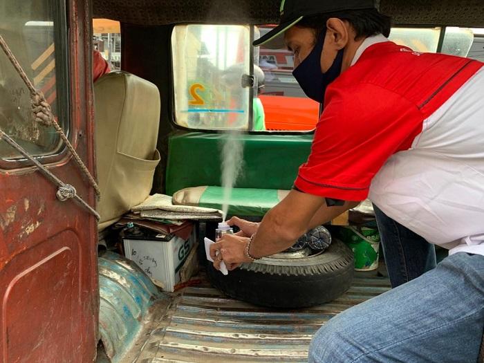 Seorang member TOSCA menyemprotkan disinfektan dalam kabin angkutan umum