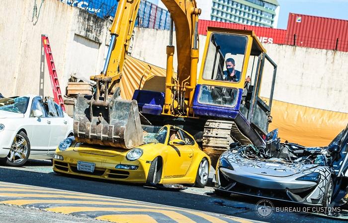 Alat berat menghancurkan mobil mewah karena dinilai ilegal oleh pemerintah Filipina