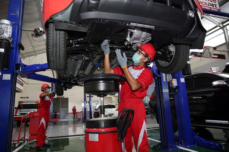 Teknisi Mitsubishi sementara memeriksa dan merawat kendaraan konsumen