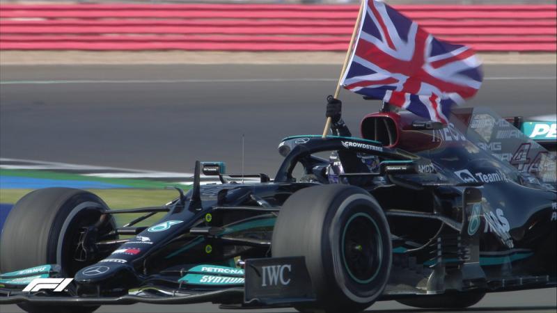 Antuasiasme Lewis Hamilton membawa bendera Inggris kala victory lap di Silverstone. (Foto: f1)