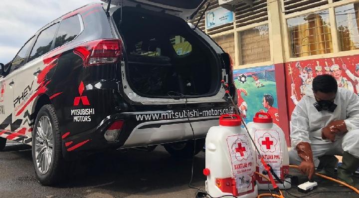 Petugas menyiapkan cairan disinfektan disemprotkan ke kendaraan konsumen Mitsubishi