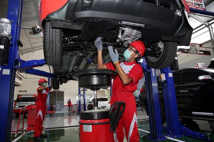 Teknisi Mitsubishi melakukan pengecekan dan perawatan mobil konsumen