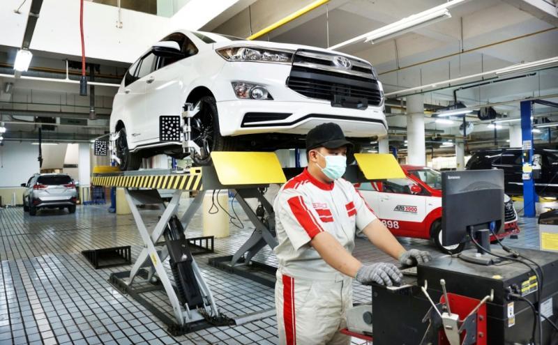 Mekanik Auto2000 sedang melakukan perawatan ban mobil Toyota kepunyaan AutoFamily