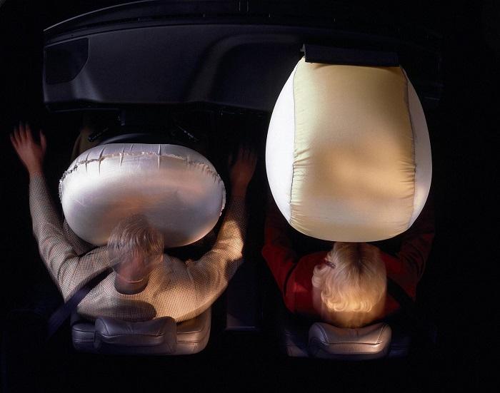 Ilustrasi pengemudi dan penumpang dengan airbag mobil yang mengembang saat benturan