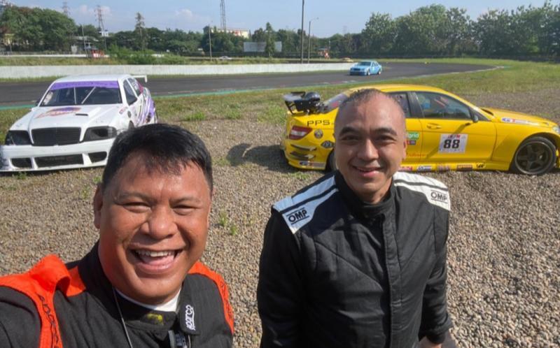 Tomi Hadi dan Ahmed Z selfie dengan latar belakang dua mobil balapnya usai sundulan. (foto : momrc)