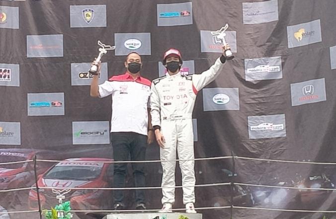 Jordan Johan bersama Dimitri Fitra Ditama manajer operasional Toyota Gazoo Racing Indonesia di podium juara kelas ITCR 1200
