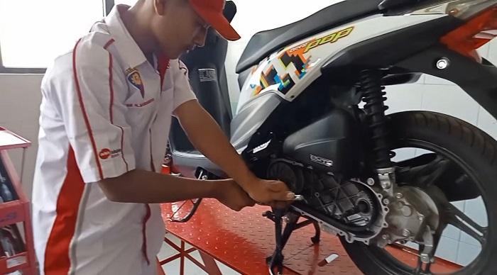 Seorang teknisi Honda sedang memeriksa dan memperbaiki motor konsumen yang bermasalah